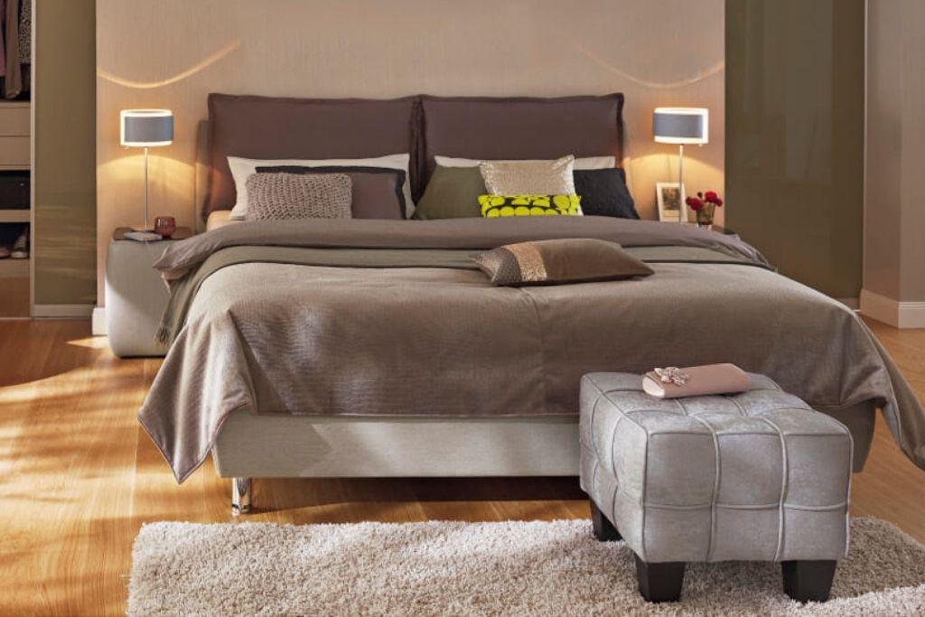 quarto com parede cinza, cama, abajures, pufes e tapetes cinzas | westwing.com.br