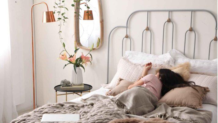 Cama com uma mulher dormindo. Na cama: travesseiros, mantas e almofadas. Ao lado da cama, mesinha lateral com vaso de flores, luminária e espelho.