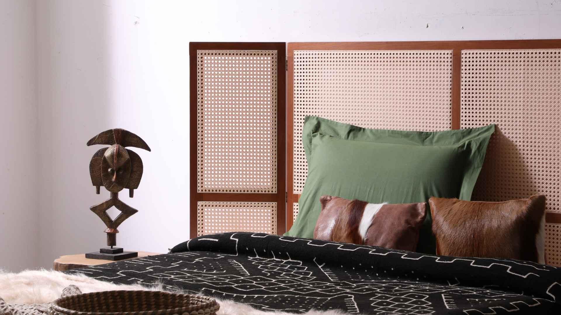 Cabeceira de madeira e palinha, travesseiros e cama arrumada com uma roupa de cama étnica, na mesinha de cabeceira tem um adorno decorativo | westwing.com.br