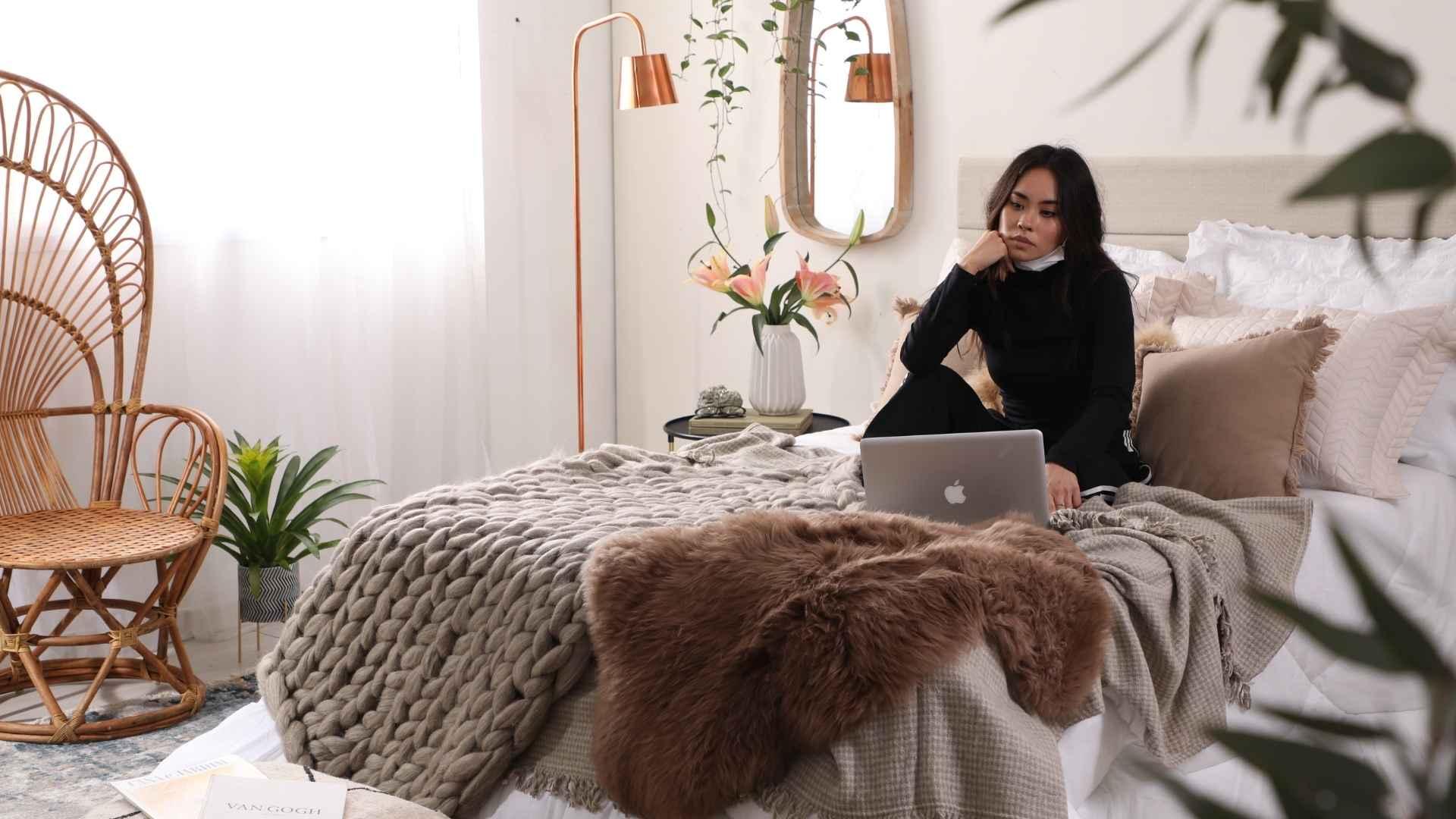 Cama com mulher sentada mexendo no computador. Sobre as camas vários cobertores e mantas. No fundo, um espelho, uma vaso com plantas em uma mesinha de cabeceira e um abajur.