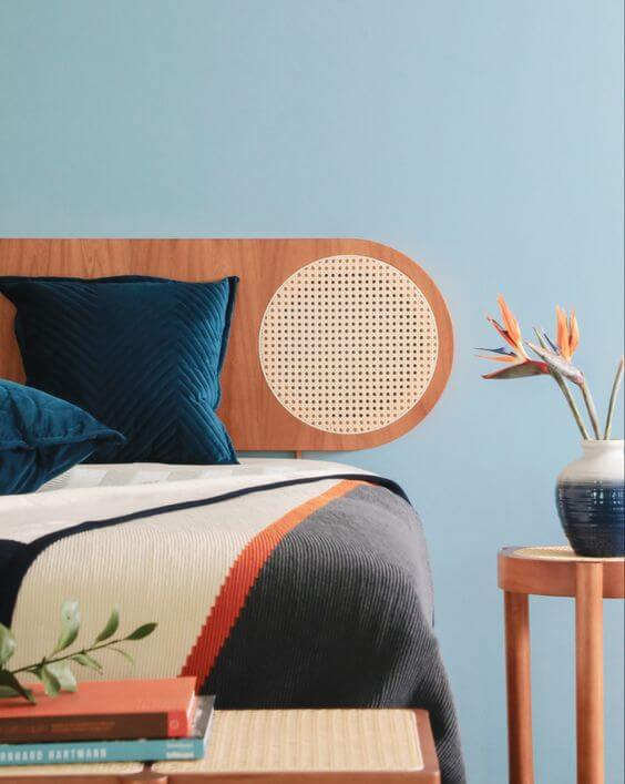 Quarto azul com cabeceira de madeira, mesa de cabeceira de madeira, almofadas azuis e vaso azul com flores | westwing.co.br