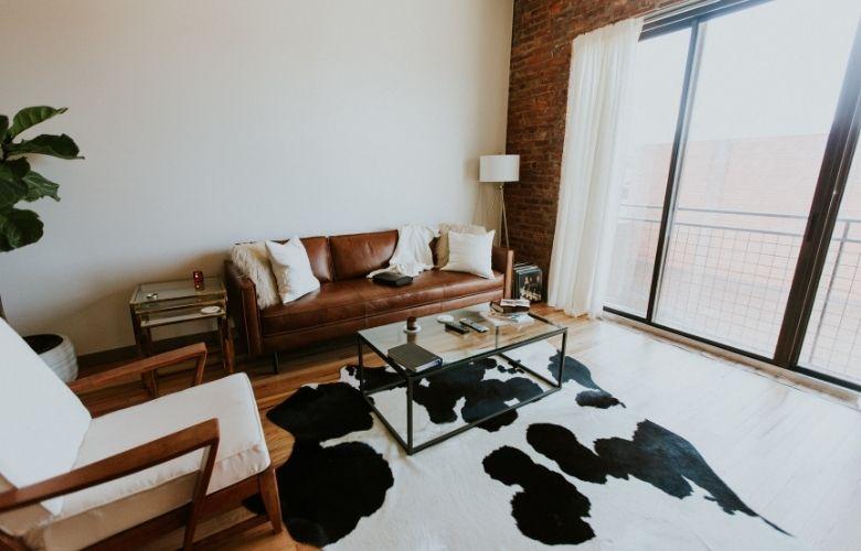 estilo industrial interiores com sofá de couro e tapete de vaquinha
