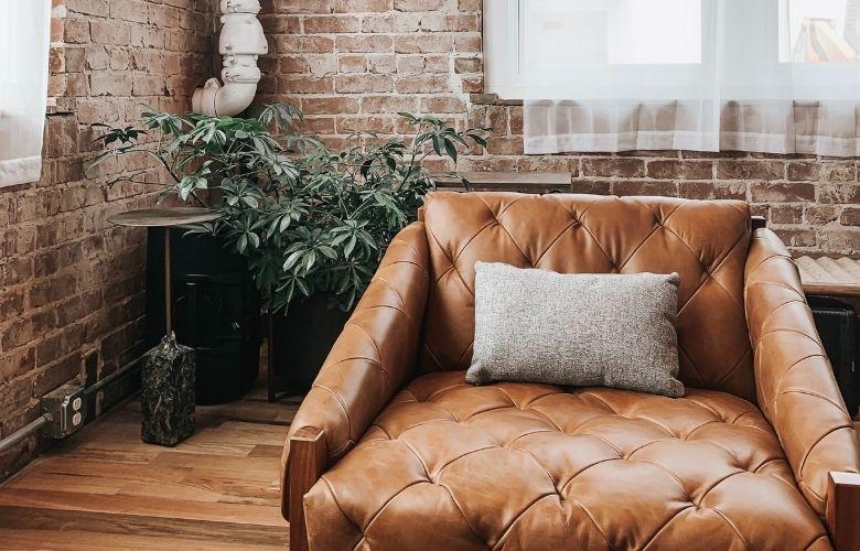 sofa industrial vintage em decoração com tijolos aparentes e planta ornamental
