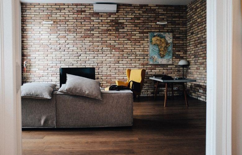parede estilo industrial de tijolos em sala de estar industrial, sofá