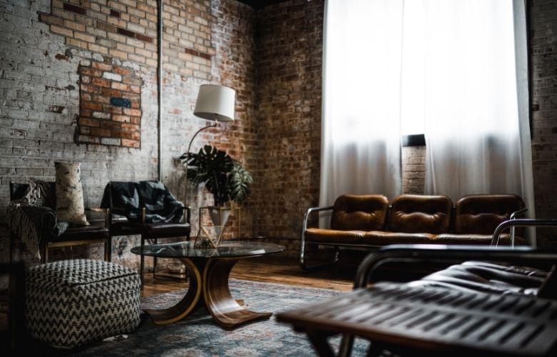 parede estilo industrial em decoração de sala de estar com sofá vintage, abajur, mesa de centro de vidro