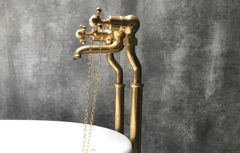 encanamento exposto no banheiro na cor dourado e parede de cimento queimado