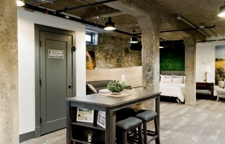 decoração industrial apartamento com bancada de madeira, banquetas, sofás, cama e quarto