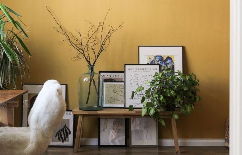 quadros decorativos estilo industrial sobre banco de madeira e vaso com planta seca