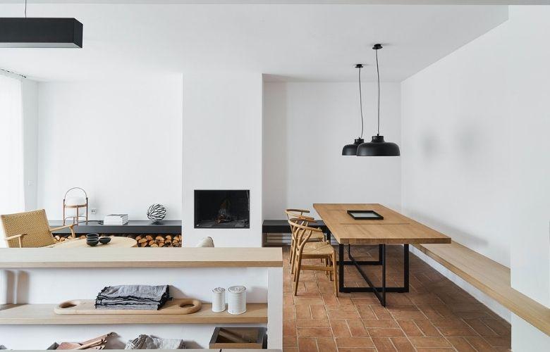 decoração tipo industrial com revestimento de piso, mesa de madeira, luminárias pendentes