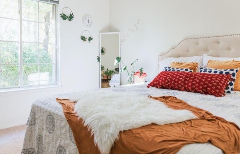 Almofada vermelha para quarto, manta laranja e decoração branca