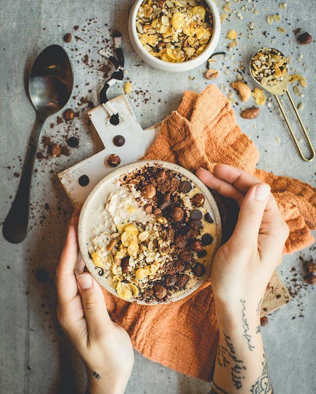 Foto de mãos segurando bowl em mesa de cimento queimado | westwing.com.br