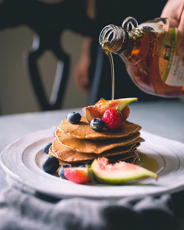 Helena Mazza dá dicas sobre food styling, foto de mel sendo derramado em panquecas com frutas vermelhas | westwing.com.br