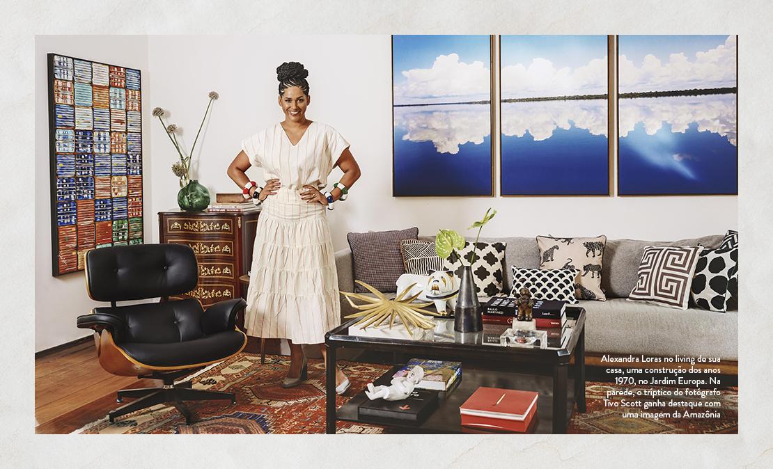 Foto de Alexandra Loras no living de sua casa, uma construção dos anos 1970, no Jardim Europa. Na parede, o tríptico do fotógrafo Tivo Scott ganha destaque com uma imagem da Amazônia