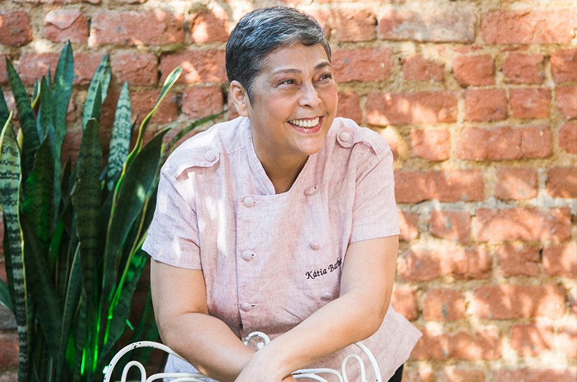 Chef Kátia Barbosa tem cabelos curtos e sorri em frente a uma parede de tijolinhos/ westwing. com.br